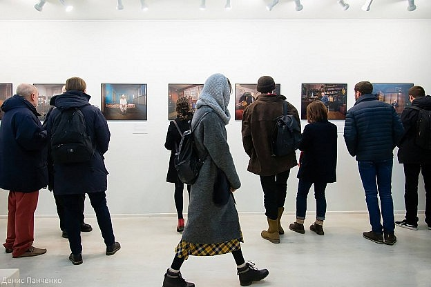 A row of people in an art gallery watching a set of photographs.