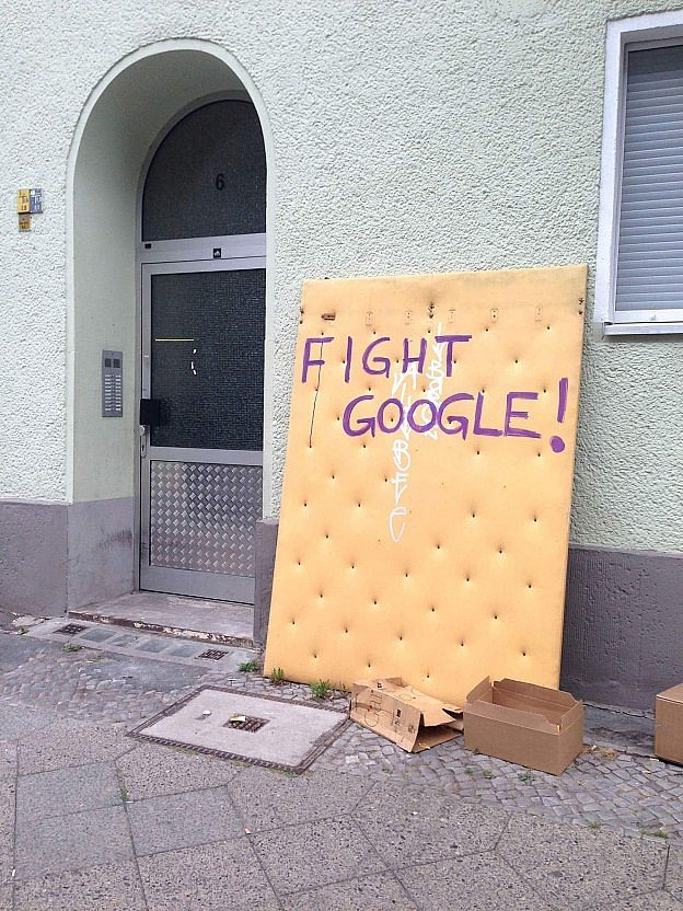 Photo showing the typical Berlin -Neukölln sight of a mattress dumped on the street, carrying a graffiti message against Google's gentrification efforts in Berlin. (You know gentrification has arrived when the old mattresses on the street look so clean as this one..)