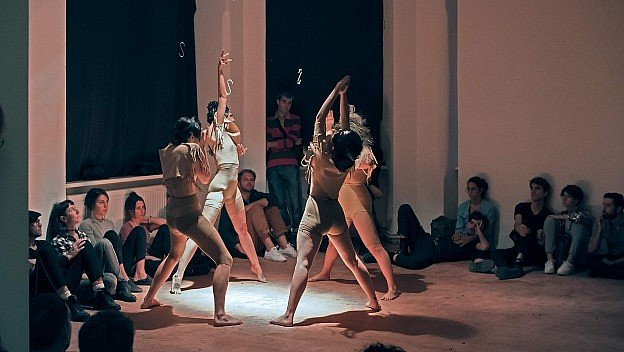 Anamnesi is a collaboration between choreographer Marta Antonucci aka Kiraly, musician Eugenio Petrarca, and visual artist T.S. Sanchez. Pictured are the female dancers surrounded by an audience seated on the floor, gazing up.