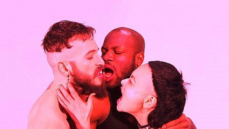 "Still image from Nicky Miller's film ""Porn Warriors"" showing a dayglo colored scene of a white guy, a black guy and a woman kissing."