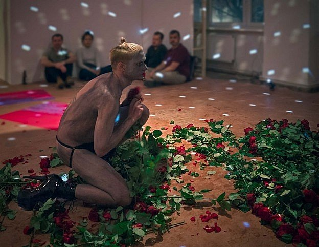 Young artist Jacob Anthony dressed in jockstrap performing in gallery in a huge filed of roses.