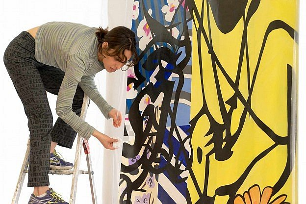 Young female artist standing on ladder installing a large colorful painting.