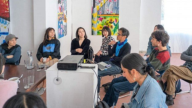 A round table table talk by young, mostly Asian artists at an exhibition space.