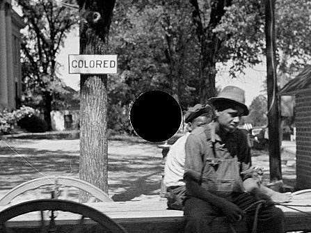 "Depression-era photo of the black kids in a park-like area, near a sign saying ""Colored."""