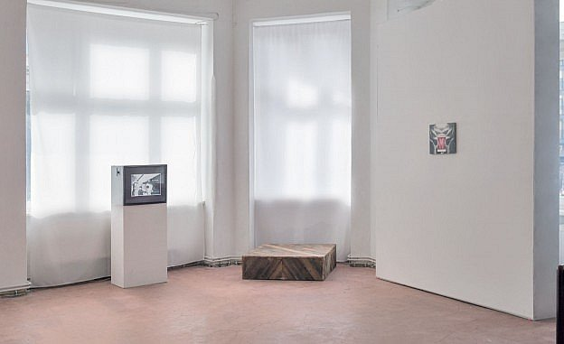 A video monitor and small painting in a spacious and bright art gallery.
