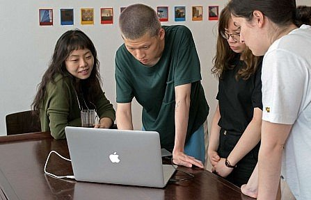 A group of Asian artist looking at a laptop screen together with their assistants.
