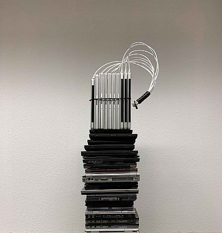 A tower of discarded laptops crowned by whips made from ethernet cable as seen at the Un_Real Desires exhibition.