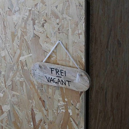 Makeshift wooden cubicle door with vacant sign at the Un_Real Desires exhibition.