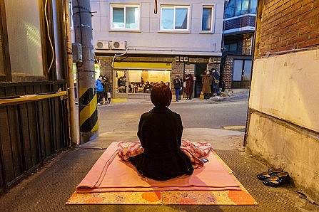 Female performance artist sitting on a blanket on the Seoul pavement, facing her audience in a storefront art gallery space, where people are sitting and watching intently.