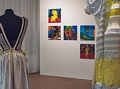 View into the Empathische Tribunale exhibition at SomoS gallery, picturing dresses by Tata Christiane and behind glass paintings by Andreas Schwarz.