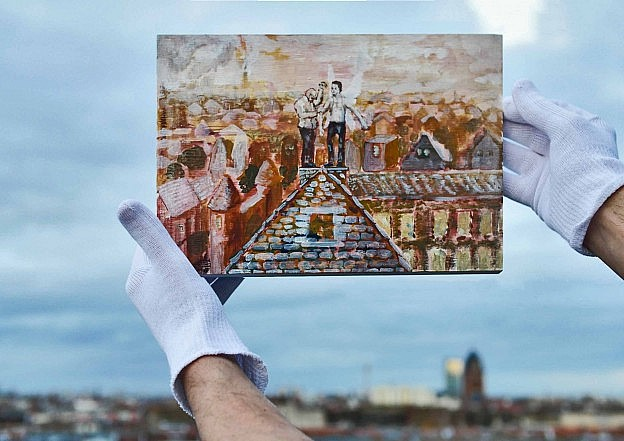 Outside color photo of white-gloved hands holding up a painting of two figures standing in a chimney, with the Berlin clouds and skyline as background.