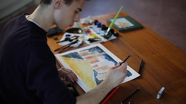 "A young white man at a desk, painting a watercolor ina still from Manami Uetake's video installation ""Imaginig Something Unknown."" -"