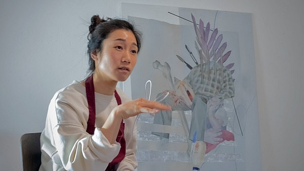 Portrait of Berlin-based South-Korean artist Jiyeon Kim speaking about her work, sitting in her atelier.