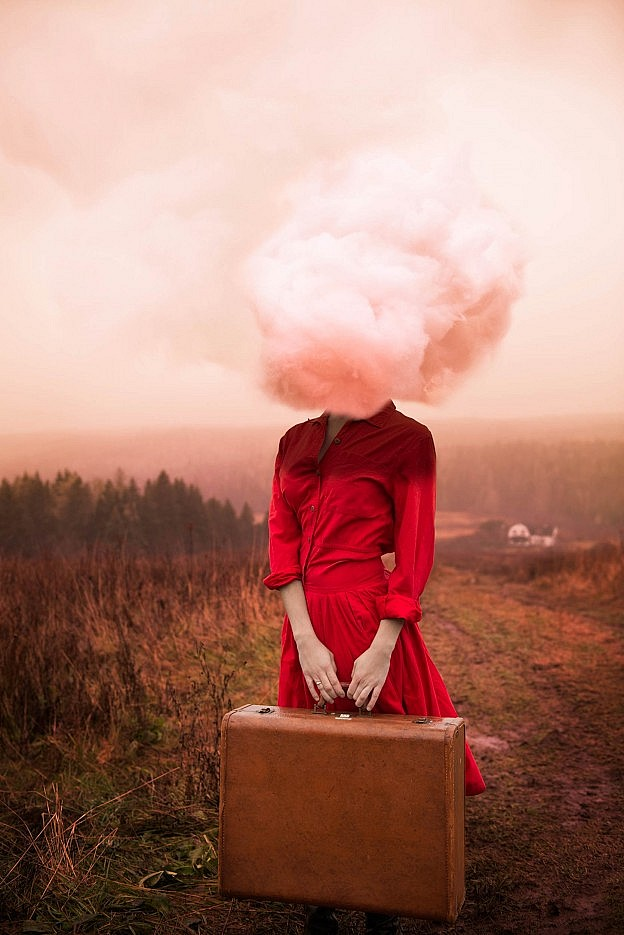 Woman with head in a cloud standing in a rural landscape holding a suitcase.
