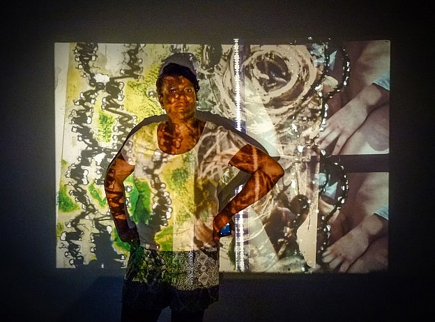 Artist Marguerite Harris in front of her projected work.