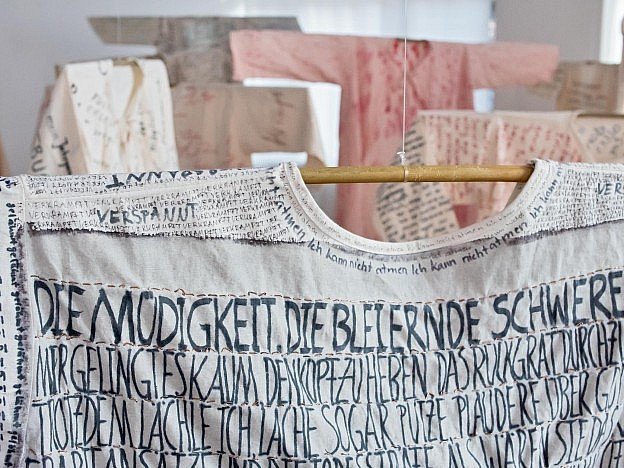 """Installation view of over-painted and customized hospital gowns from Artist Hannah Santana's art project """"How Does it Feel?"""" at SomoS Berlin, July 2020."""