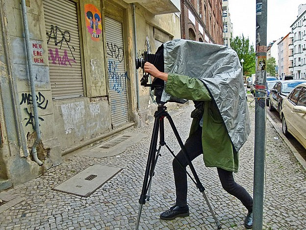 Dirty urban street with parka-clad photographer Donato Del Giudice hidden under the cloth of a large format camera.